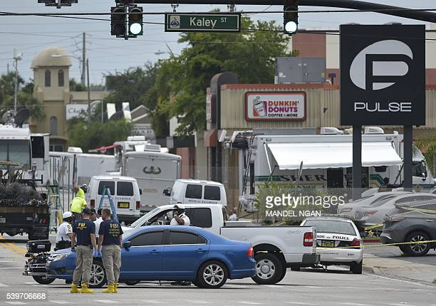 Police and investigators work near the area of the mass shooting at the Pulse nightclub on in Orlando Florida on June 12 2016 A somber President...