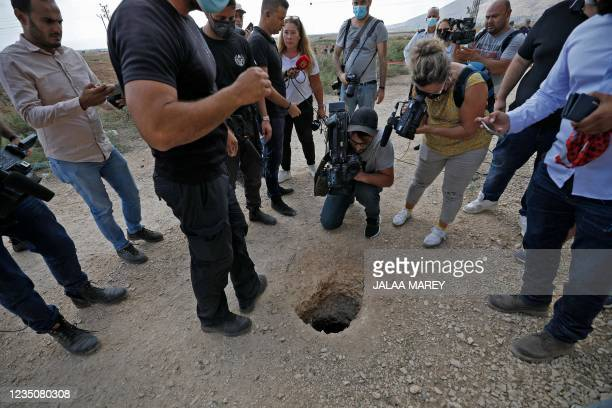 Police and journalists gather around a hole used by six Palestinians to escape from the Gilboa Prison after they dug a tunnel beneath a sink, in...
