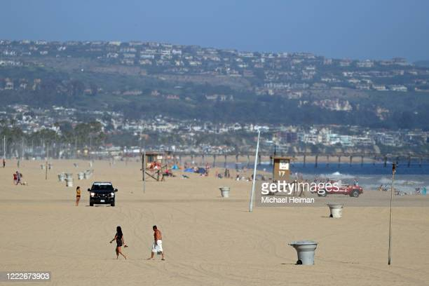 Police and lifeguards patrol as people walk on the beach south of Newport Pier on May 3 2020 in Newport Beach California California Gov Gavin Newsom...