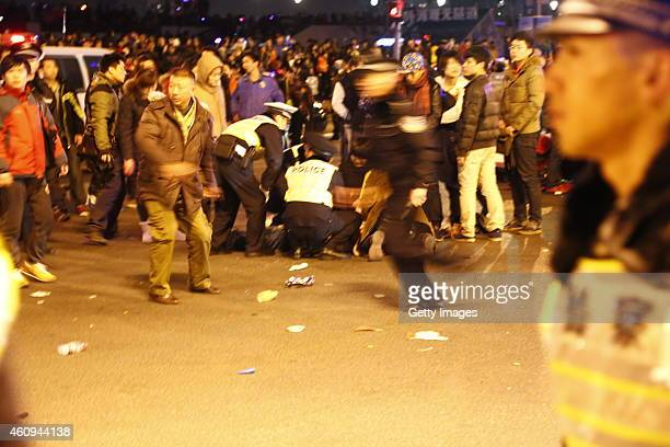 Police and medical staff give firstaid to the people injured during a stampede at Shanghai's New Year celebration at the Bund area on January 1 2015...