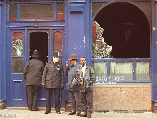 Police and members of the local community chat outside the burnt out Atlantic Pub 14 December following the overnight riots in the streets of Brixton...