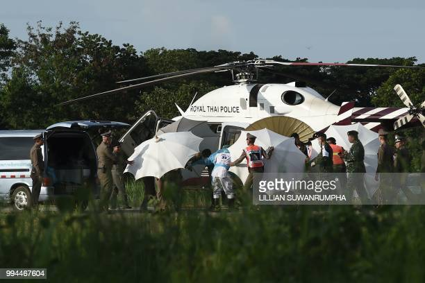 TOPSHOT Police and military personnel use umbrellas to cover around a stretcher near a helicopter and an ambulance at a military airport in Chiang...