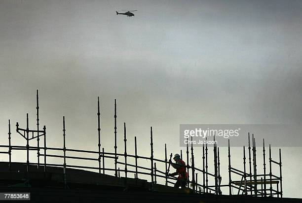 Police and news helicopters hover overhead as construction labourers work on scaffolding at a construction site on November 12 2007 in East London...