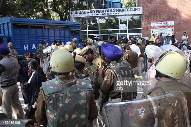 Police and onlookers gather outside as controversial Indian guru Rampal Maharaj arrives at the Punjab and Haryana High Court in Chandigarh on...