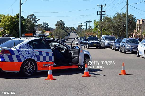 Police and other law enforcment agencies corden off a street as forensic experts collect evidence inside a house in the Guildford area of Sydney on...