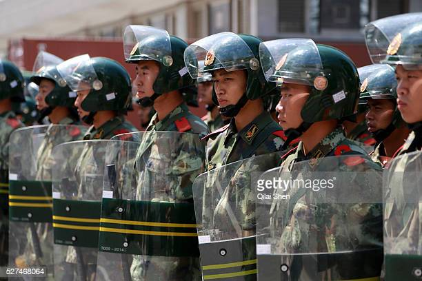 Police and paramilitary forces stand watch as protestors display banners and pictures of Chairman Mao while chanting slogans during their march...