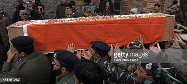 Police and paramilitary officers carry the coffin of martyr Assistant SubInspector Kafeel Ahmad during a wreath laying ceremony on January 7 2014 in...