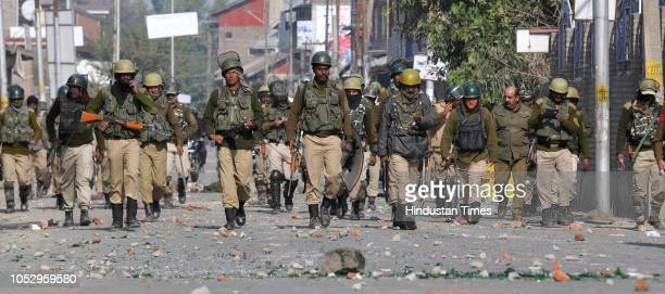 Police and paramilitary soldiers walk on a road dotted with stones bricks and glass thrown at them by protesters during a protest near the encounter...
