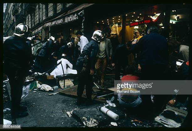 Police and passersby crowd around the entrance of the Tati department store on Rue de Rennes after a bomb explodes projecting debris onto the street...