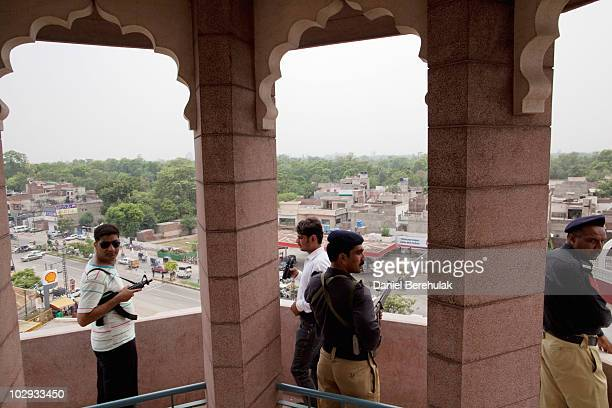 Police and private security guards keep watch from the turret of the Garhi Shahu mosque as members of the persecuted Ahmadiyya community gather for...