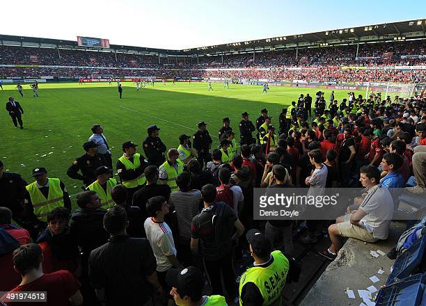 Police and private securitymen contain spectators after a barrier collapsed during the La Liga match between CA Osasuna and Real Betis Balompie at...