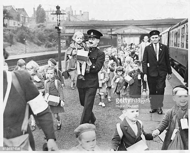 Police and railwaymen escort children at Ealing Station as they are evacuated to safer destinations September 1939 | Location Ealing Broadway Ealing...