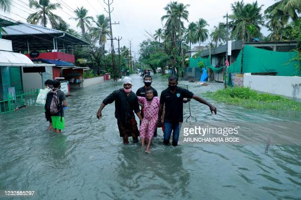 Police and rescue personnel evacuate a local resident through a flooded street in a coastal area after heavy rains under the influence of cyclone...