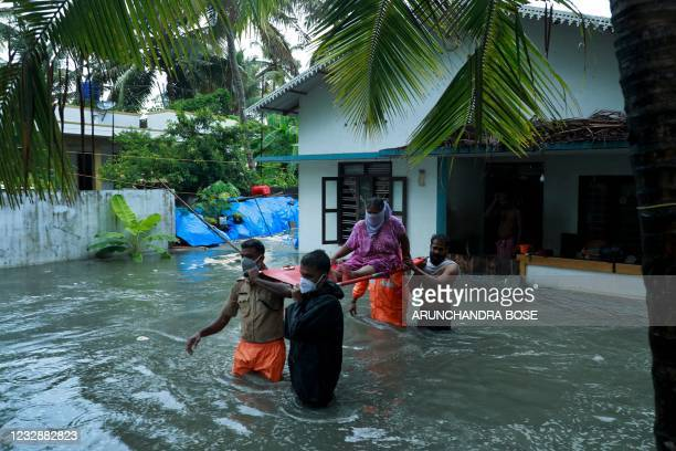 Police and rescue personnel evacuate local residents from a flooded house in a coastal area after heavy rains under the influence of cyclone...