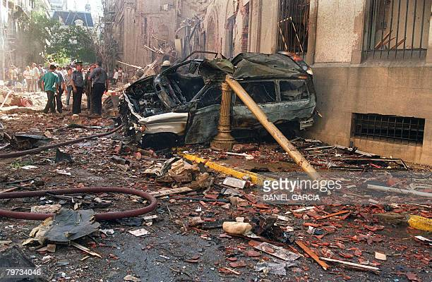 Police and rescue workers stand near destroyed cars and debris on March 17 1992 in Buenos Aires shortly after a powerful bomb ripped through the...