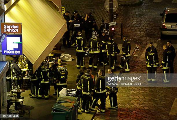 Police and rescuers are seen outside a cafe-brasserie in10th arrondissement of the French capital Paris, on November 13, 2015. At least 18 people...