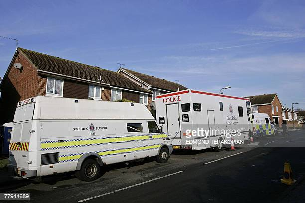 Police and scientific vehicles are stationned in front of a house in Margate on the southeast English coast 16 November 2007 after British police...
