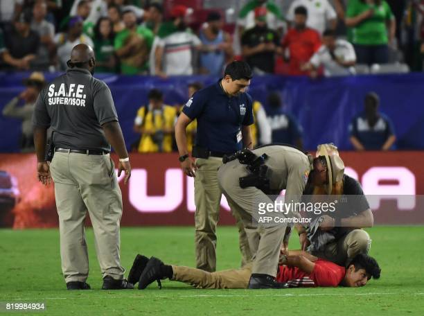 Police and security arrest a fan who ran onto the field at the end of the Mexico vs Honduras quarter final game during the 2017 CONCACAF Gold Cup at...