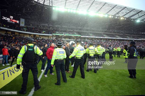 Police and security contain Mansfield fans after a final whistle pitch invasion at the Sky Bet League Two match between Milton Keynes Dons and...