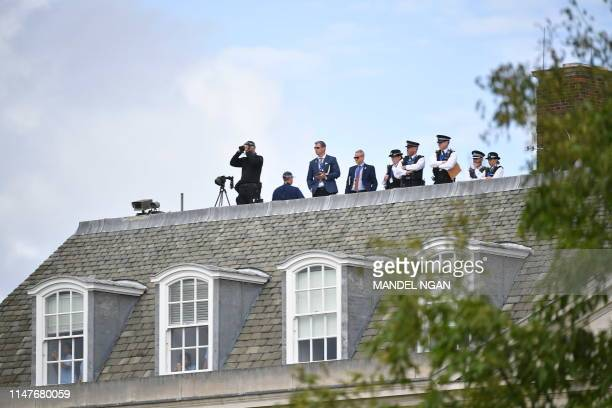 Police and security personnel survey the area from the top of Winfield House the residence of the US Ambassador in London on June 3 as US President...