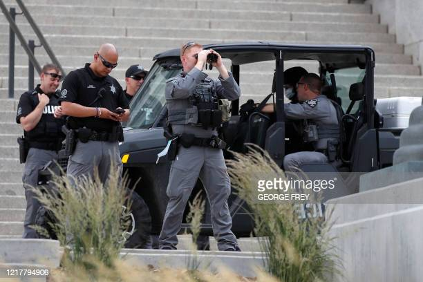Police and security personnel watch over a protest crowd in front of the Utah State Capitol building during a protest in Salt Lake City, Utah on June...