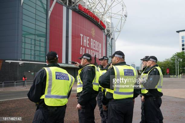 Police and security staff stand guard outside Old Trafford Stadium ahead of the Premier League match between Manchester United and Leicester City on...
