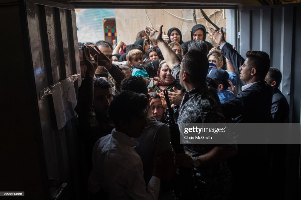 Police and security staff try to keep people from forcing their way into a voting station on September 25, 2017 in Erbil, Iraq. Despite strong objection from neighboring countries and the Iraqi government, some five million Kurds took to the polls today across three provinces in the historic independence referendum.