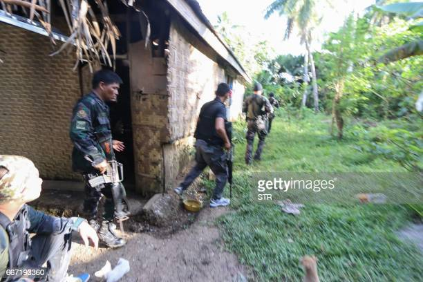 Police and soldiers take position as they engage with the Abu Sayyaf group in the village of Napo Inabanga town Bohol province in the central...