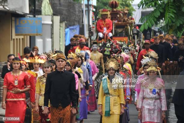 Police and soldiers wearing traditional outfits participate in a parade as Indonesia's President Joko Widodo and First Lady Iriana Widodo take part...