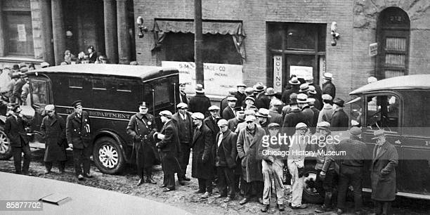Police and spectators gather in front of the infamous garage where the St Valentine's Day Massacre occurred Chicago 1929 The event became a symbol of...