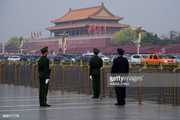 A police and two paramilitary police officers take position near Tiananmen Square in Beijing on March 27 2018 Speculation intensified on March 27...