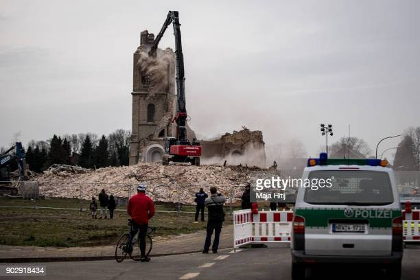 Police and visitors stand nearby as an excavator demolishes Saint Lambertus church following protests by activists on January 9 2018 in Immerath...