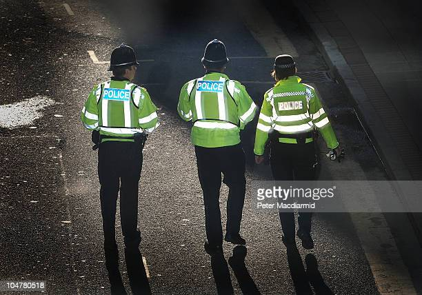 Police are lit by reflected window light as they patrol next to the Conservative Party Conference on October 4, 2010 in Birmingham, England. On the...