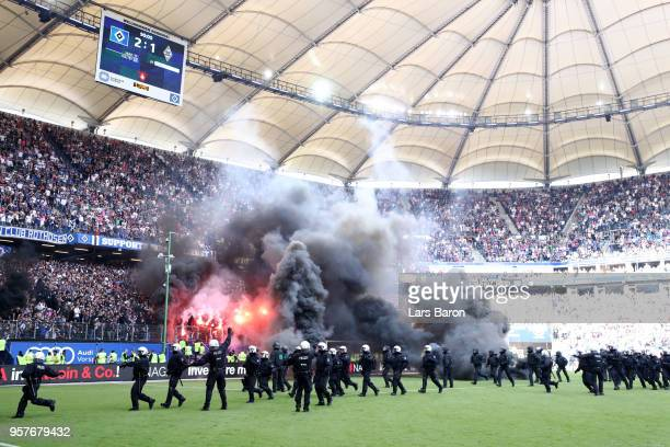 Police are seen as fans throw flares onto the pitch during the Bundesliga match between Hamburger SV and Borussia Moenchengladbach at...