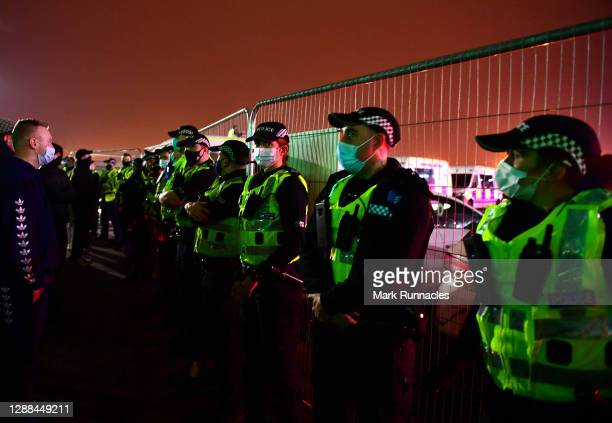 Police are seen guarding fans outside the stadium following the Betfred Cup match between Celtic and Ross County at Celtic Park on November 29, 2020...