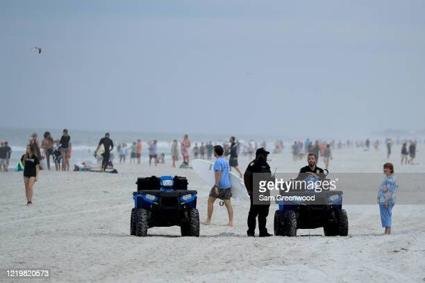 Police are seen speaking to people at the beach on April 19 2020 in Jacksonville Beach Florida Jacksonville Mayor Lenny Curry announced Thursday that...