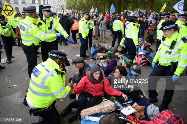 Police arrest a climate activist near Downing Street during the third day of climate change demonstrations by the Extinction Rebellion group in...