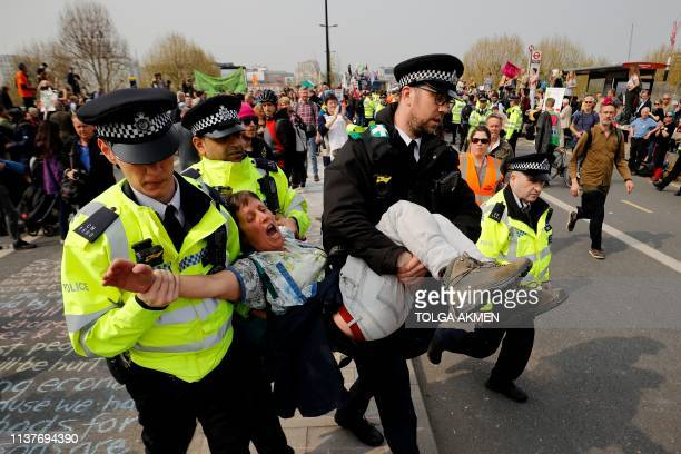 TOPSHOT Police arrest a climate change activist blockading Waterloo bridge on the third day of an environmental protest by the Extinction Rebellion...