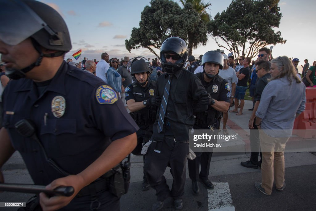 Police arrest a Conservative demonstrator at an 'America First' demonstration on August 20, 2017 in Laguna Beach, California. Organizers of the rally describe it as a vigil for victims of illegal immigrants and refugees. Opponents say the demonstration is steeped in racism.