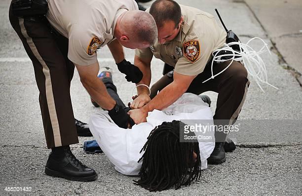 Police arrest a demonstrator during a protest along Interstate Highway 70 on September 10 2014 near Ferguson Missouri The demonstrators had planned...