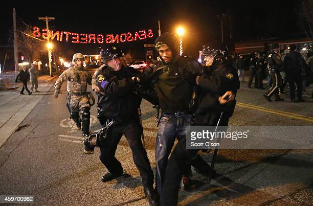 Police arrest a demonstrator outside the police station November 28, 2014 in Ferguson, Missouri. The Ferguson area has been struggling to return to...