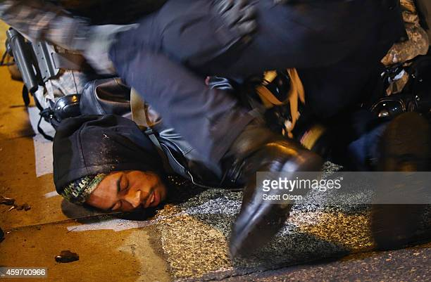 Police arrest a demonstrator outside the police station November 28 2014 in Ferguson Missouri The Ferguson area has been struggling to return to...