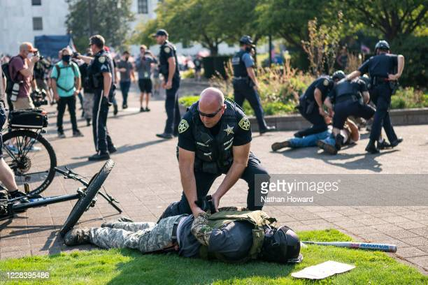 Police arrest a far-right protester after a clash with counter protesters during a rally on September 7, 2020 in Salem, Oregon. A Pro-Trump caravan...