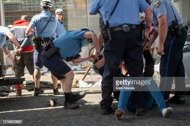 Police arrest a man and woman during widespread unrest following the death of George Floyd on May 31 2020 in Philadelphia Pennsylvania Protests have...