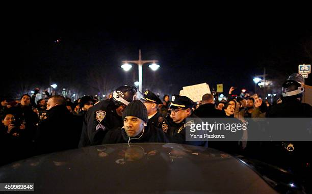 Police arrest a man on a passenger car in traffic standstill on the West Side Highway during a protest December 4 2014 in New York City Protests...