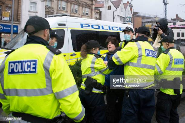 Police arrest a man who was wearing a wig during the anti-lockdown protest on November 14, 2020 in Bristol, England. Police had warned protesters to...