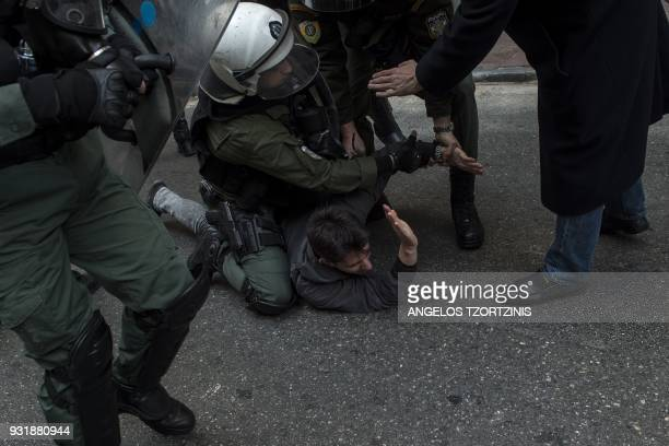 TOPSHOT Police arrest a protester during a demonstration against home auctions in Athens on March 14 2018 Protesters are opposing the auction of...
