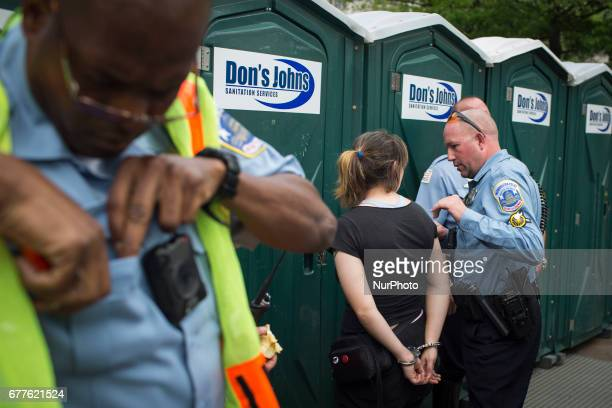 Police arrest a protester during a massive protest against the racist policies of the current president Donald Trump on 1st May 2017 in Washington DC