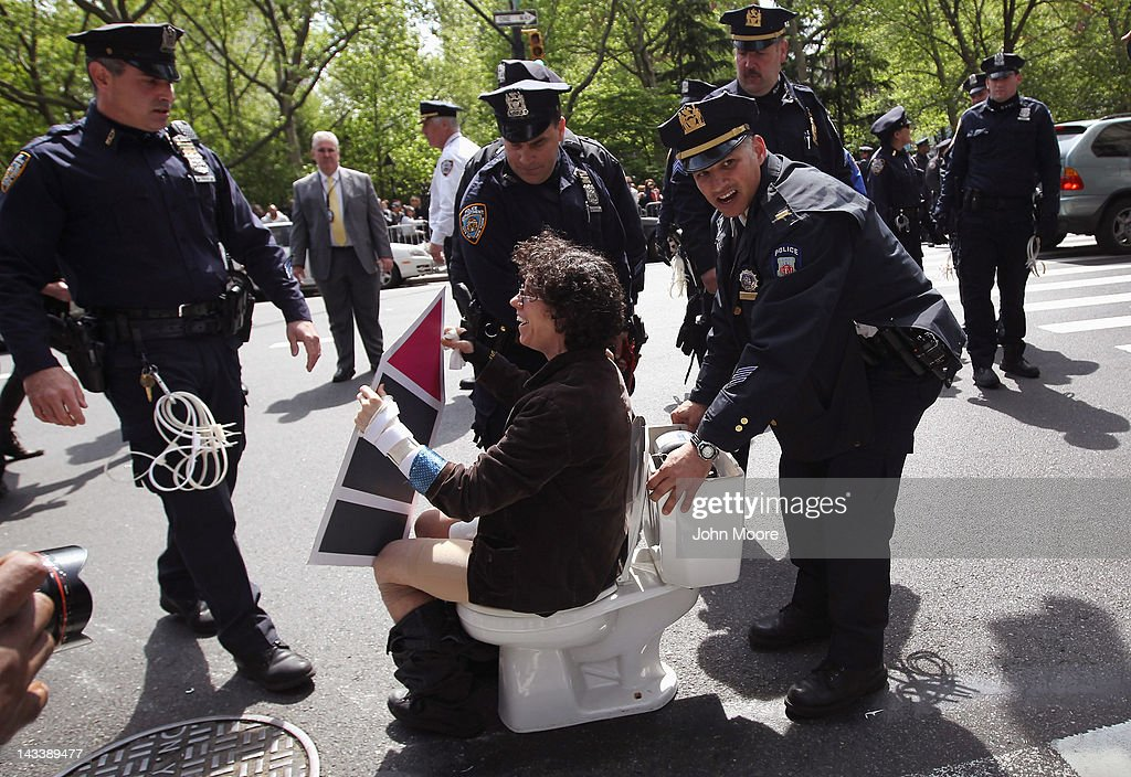 Police arrest a protester during an ACT-UP and Occupy Wall Street demonstration on April 25, 2012 in New York City. Police arrested several protesters who chained themselves to toilets and furniture, saying that people with AIDS are 'being kicked to the curb' by Mayor Bloomberg due to recent policy changes in New York City. ACT-UP (AIDS Coalition to Unleash Power), was marking their 25-year anniversary in supporting services for people with AIDS worldwide. They were joined by Occupy Wall Street protesters in a march from New York's city hall to Wall Street. The groups called for a tax on Wall Street transactions and speculative trades to raise money for to end the global AIDS epidemic and provide universal healthcare in the U.S.