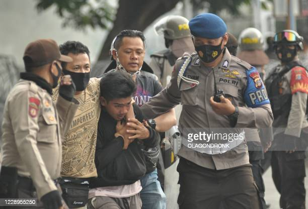 Police arrest a protester following clashes during a nationwide strike against a new law which critics fear favours investors at the expense of...